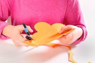 Zeichnen Sie eine große Blume auf das orangefarbene Tonpapier und schneiden Sie diese aus.