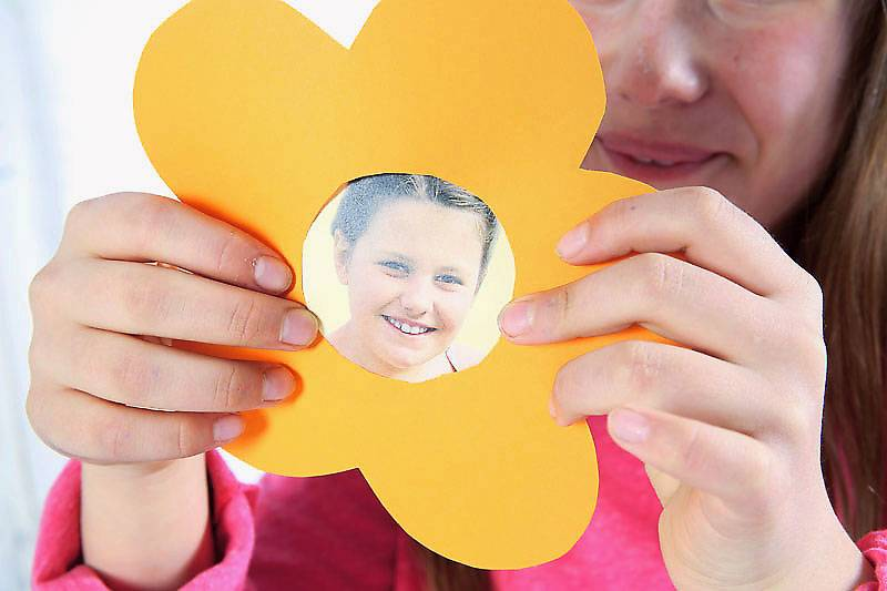 Lassen Sie nun Ihr Kind das Foto hinter die Blüte kleben.