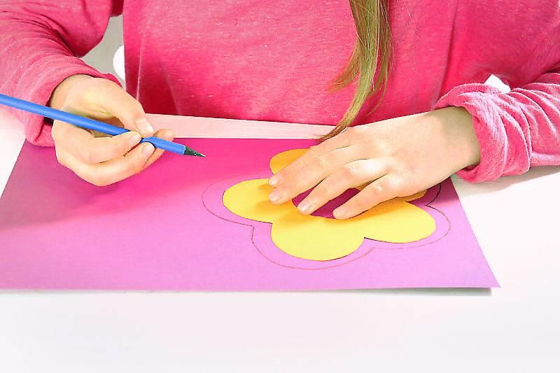 Legen Sie die Blume auf das pinkfarbene Papier und zeichnen Sie eine zweite Blume, die etwas größer ist als die erste.