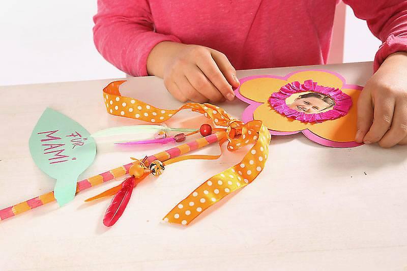 Kleben Sie Blume und Blatt mit Klebeband an den Holzstab und binden Sie eine hübsche Schleife darum.