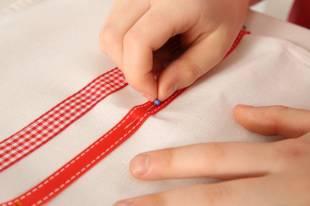 Stecken Sie die beiden Bänder nebeneinander etwa 10 cm vom unteren Rand des Tuches mit Stecknadeln fest.