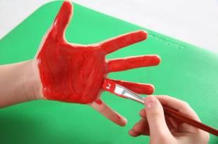 Malen Sie eine Handfläche Ihres Kindes mit Stofffarbe an...
