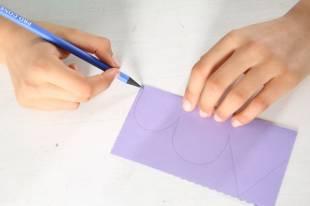 Zeichnen Sie auf einer Hälfte vom Falz weg eine halbe Schmetterlingsform – oben eine Spitze und darunter zwei kleinere Bögen.