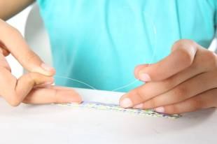 In der Mitte binden Sie eine Nylonschnur fest, schieben auf beide Enden eine kleine Perle...